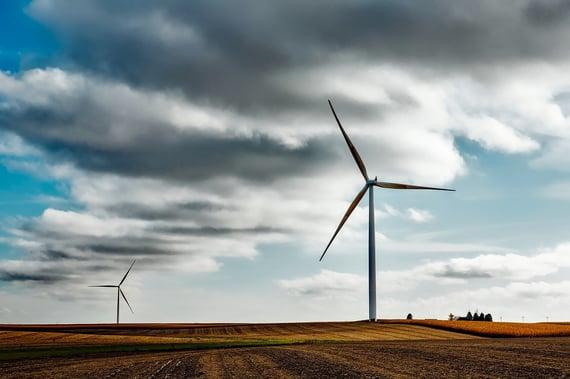 Wind energy spinning turbines on farm against cloudy sky